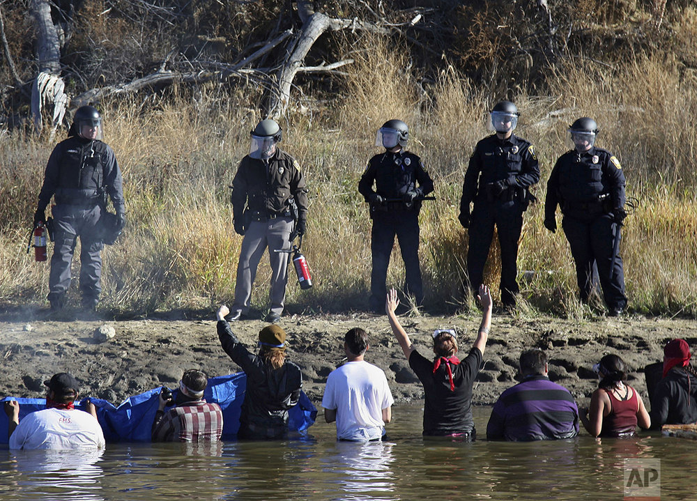 Dozens of protestors demonstrating against the expansion of the Dakota Access Pipeline wade in cold creek waters confronting local police, as remnants of pepper spray waft over the crowd near Cannon Ball, N.D., Wednesday, Nov. 2, 2016. (AP Photo/John L. Mone)