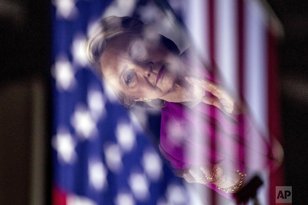 Democratic presidential candidate Hillary Clinton, seen in a reflection, applauds as Sen. Bernie Sanders, D-Vt., speaks at a rally at Coastal Credit Union Music Park at Walnut Creek in Raleigh, N.C., Thursday, Nov. 3, 2016. (AP Photo/Andrew Harnik)