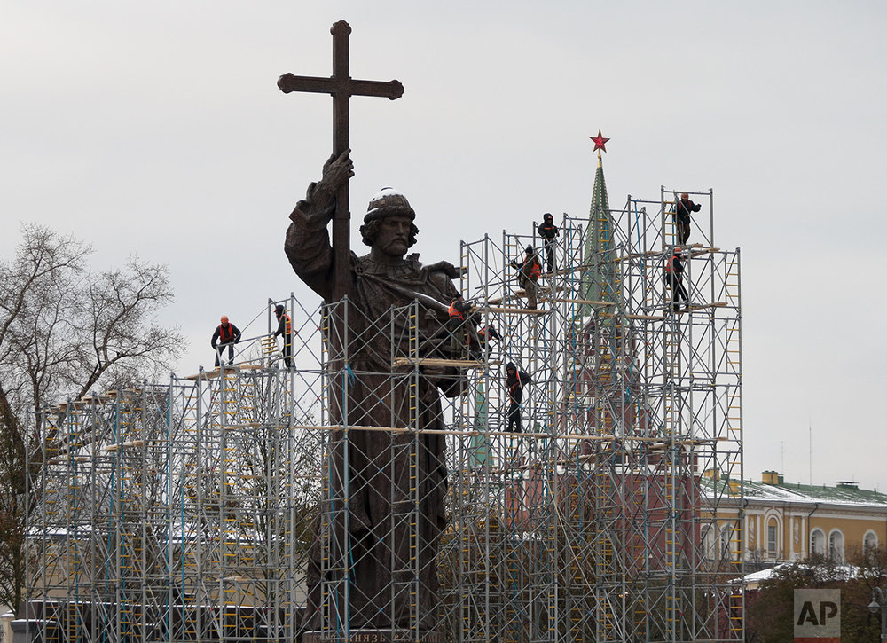 Municipal workers disassemble scaffolding around a monument to Vladimir the Great, who brought Christianity to pagan Kievan Rus in the 10th century, in downtown Moscow, Russia on Tuesday, Nov. 1, 2016. The official opening ceremony was held on Friday, when Russia celebrated National Unity Day. The Kremlin is in the background. (AP Photo/Ivan Sekretarev)