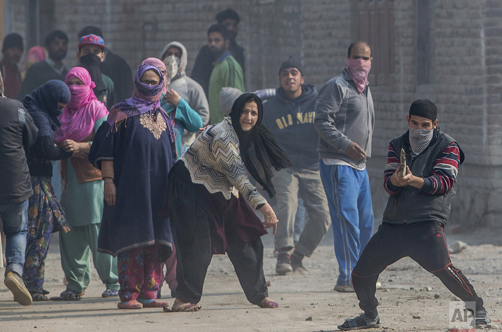 In this Wednesday, Nov. 2, 2016 photo, a Kashmiri Muslim protester, right, taunts Indian security personnel as a woman throws a stone at them during a raid carried out to arrest suspected protesters in the outskirts of Srinagar, Indian controlled Kashmir. More than 8,000 people, mostly teenaged boys and young men, have already been rounded up and put in jail in India's largest-ever crackdown on unarmed civilians, launched to quell an anti-India uprising that has kept this Himalayan territory in a virtual lockdown since July. (AP Photo/Dar Yasin)