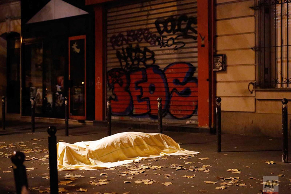 In this Friday Nov. 13, 2015 photo a victim under a blanket lays dead outside the Bataclan theater in Paris. It was close to midnight on a busy, mild November Friday as Paris reeled after learning men with bombs and guns had attacked popular bars, France's national stadium and the Bataclan concert hall. (AP Photo/Jerome Delay)