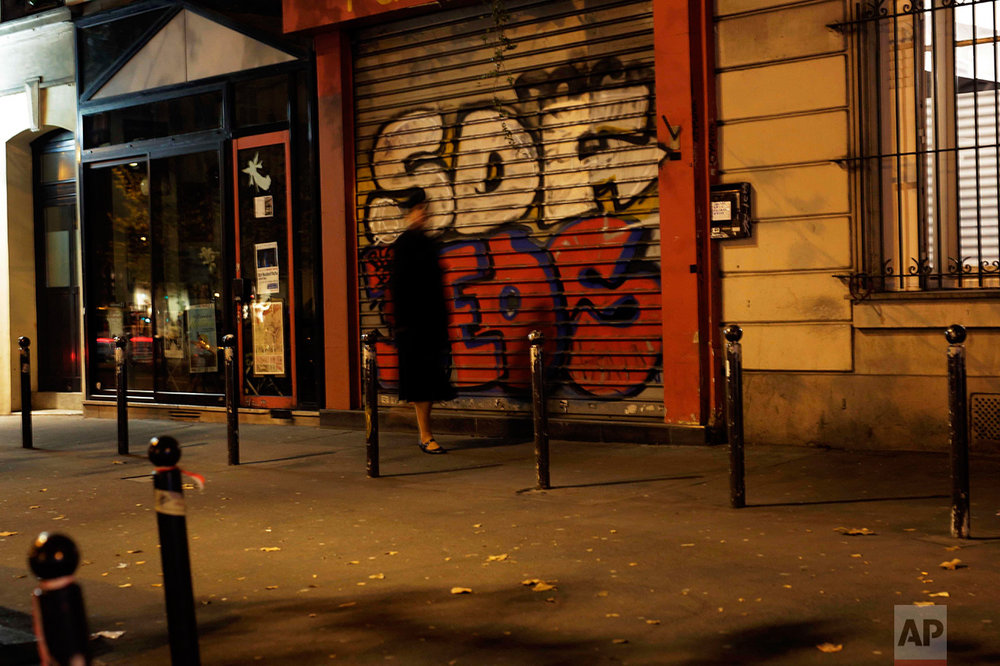 A woman walks Sunday Nov. 6, 2016, on the very spot where a victim of a series of shootings laid dead under a blanket in Paris, Friday Nov. 13, 2015. It was close to midnight on a busy, mild November Friday as Paris reeled after learning men with bombs and guns had attacked popular bars, France's national stadium and the Bataclan concert hall. (AP Photo/Jerome Delay)