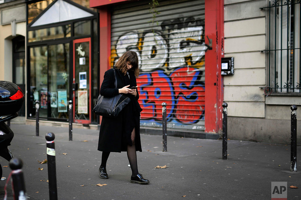 A woman walks Saturday Nov. 5, 2016, past the very spot where a victim of a series of shootings laid dead under a blanket in Paris, Friday Nov. 13, 2015. The identity of the lone body in the street, has never been publicly revealed, though the photo of it shot by Associated Press photographer Jerome Delay was one of the iconic images from that night. (AP Photo/Jerome Delay)