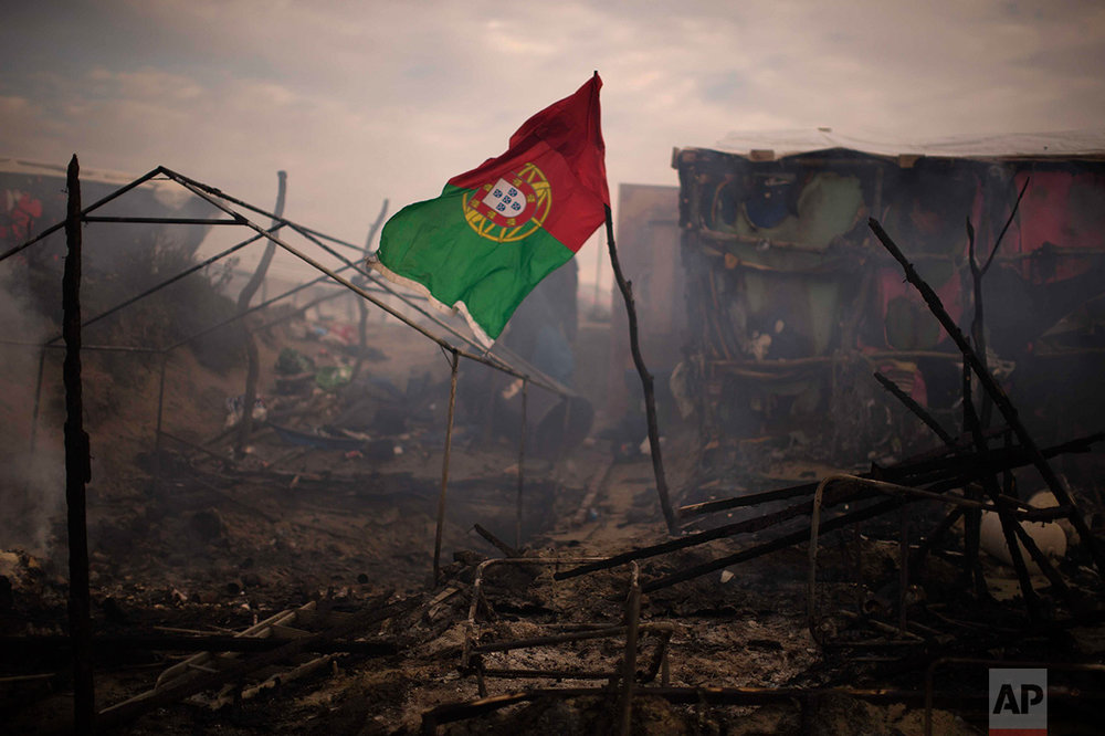 "In this Wednesday, Oct. 26, 2016 photo, a flag of Portugal waves next to burning tents, abandoned by their owners at the makeshift migrant camp known as ""The jungle"" near Calais, northern France. (AP Photo/Emilio Morenatti)"