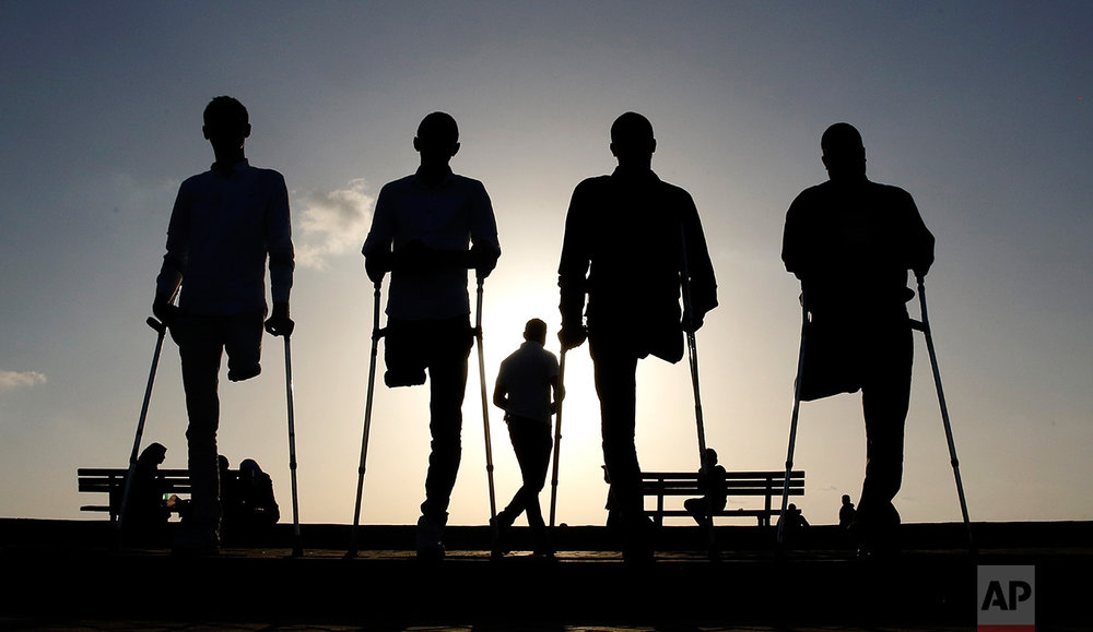 Four Palestinian friends who were injured during conflicts walk by the sea at Gaza's small fishing harbor, Monday, Oct. 24, 2016. Fighting left thousands of people with disabilities or no limbs in this Palestinian enclave. (AP Photo/Hatem Moussa)