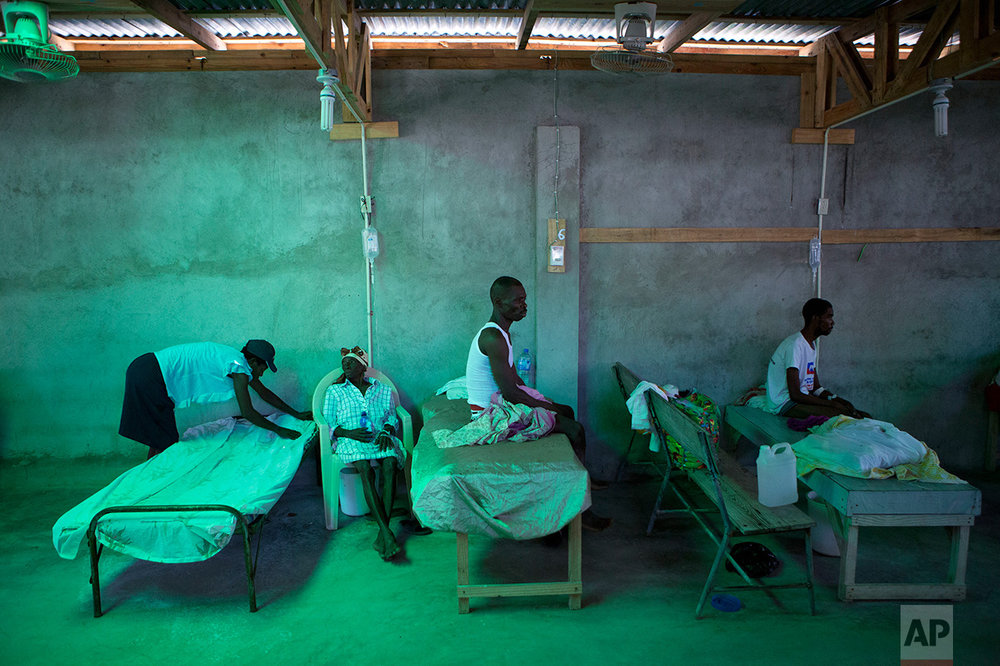 The daughter of 84-year-old Armant Germain replaces the sheets on her bed, in the cholera ward at a hospital in Les Cayes Haiti, Tuesday, Oct. 11, 2016. Health authorities have warned that Hurricane Matthew has created conditions that are likely to cause an increase in the deadly waterborne cholera virus. (AP Photo/Rebecca Blackwell)