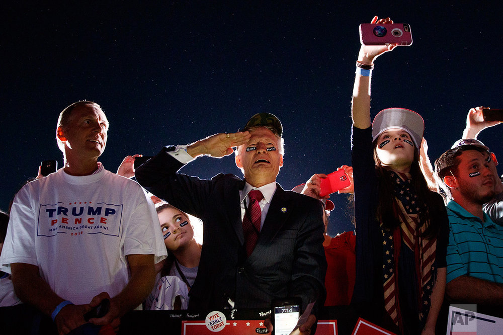 Jeff Muller of Wilmington, N.C., salutes as Republican presidential candidate Donald Trump arrives to a campaign rally, Wednesday, Oct. 26, 2016, in Kinston, N.C. (AP Photo/Evan Vucci)