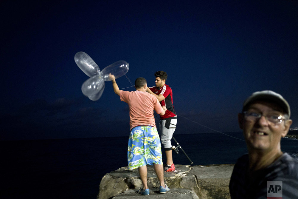 This Nov. 12, 2016 photo shows Derek Aguiar Gonzalez, a stomatology student and amateur fisherman who said he takes home what he catches, preparing to cast his line, fitted with inflated condoms that serve to keep the bait high in the water and increase the line's resistance against the pull of heavy fish, at the malecon seawall in Havana, Cuba.  (AP Photo/Ramon Espinosa)