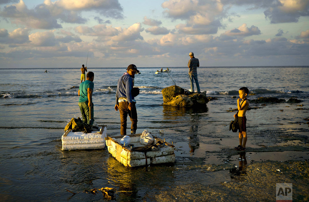 "In this Nov. 11, 2016 photo, young fishermen pull their rafts made out of foam as they head to sea from Chivo Beach in Havana, Cuba. Many Cubans have taken to riding out on blocks of industrial foam to catch larger fish, but the unsafe technique known as ""cork fishing"" has become the target of frequent coast guard crackdowns with steep fines. (AP Photo/Ramon Espinosa)"