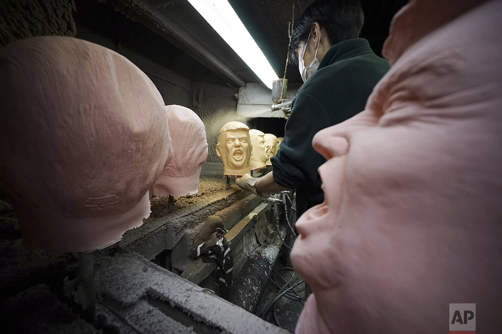 A worker spray paints rubber masks depicting President-elect Donald Trump on a production line at the Ogawa Studio in Saitama, north of Tokyo, Tuesday, Nov. 15, 2016. Ogawa Studio, the only manufacturer of rubber masks in Japan, is working non-stop to catch up with a flood of orders for Trump masks since his election victory a week earlier. Twenty three workers are trying to produce 350 likenesses of Trump a day, up from 45 before the U.S. election, factory executive manager Takahiro Yagihara said Tuesday. (AP Photo/Eugene Hoshiko)
