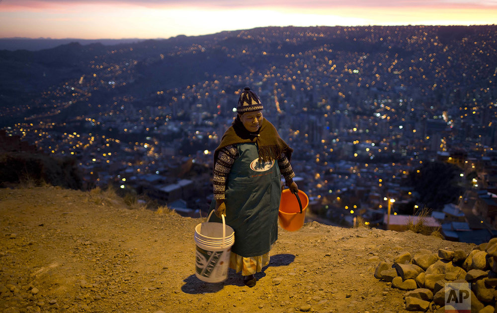 A woman walks with two buckets to wait for a water tank to arrive near her neighborhood in La Paz, Bolivia, Wednesday, Nov. 16, 2016. Bolivia's President Evo Morales asked for forgiveness from residents of the city for water shortages caused by the worst drought in 25 years and acknowledged that there are no immediate solutions. (AP Photo/Juan Karita)