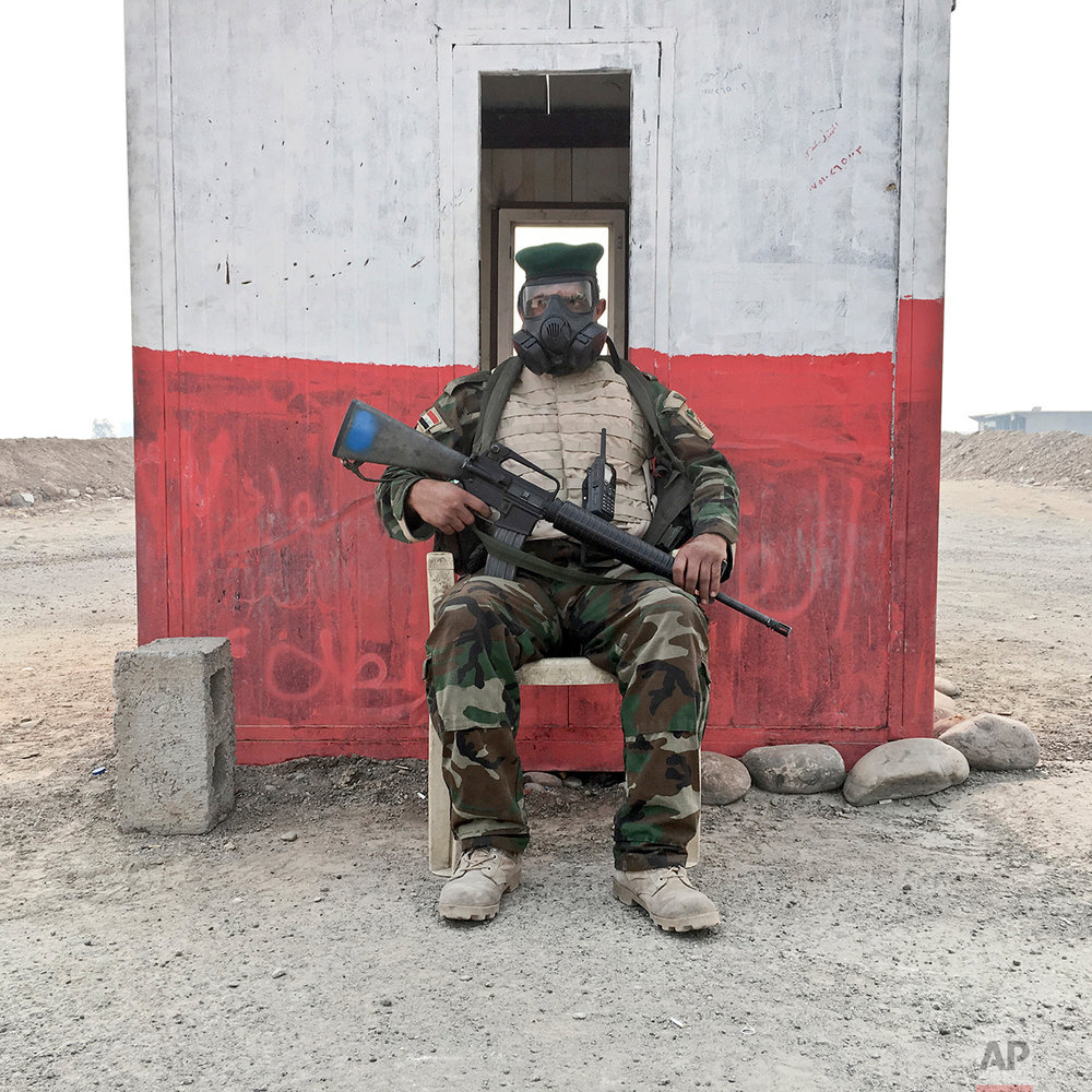 In this photo taken Friday, Oct. 21, 2016, Raad Muqdam al-Mosieh, 35, from Baghdad, Iraq, an Iraqi army soldier, poses for a portrait as he guards a checkpoint while wearing a gas mask on the outskirts of Qayara, some 50 kilometers south of Mosul, Iraq. The push to kick the Islamic State out of Mosul has brought together an eclectic mix of Iraqis, young and old, police and soldiers, and a variety of irregular uniforms and equipment. (AP Photo/Marko Drobnjakovic)