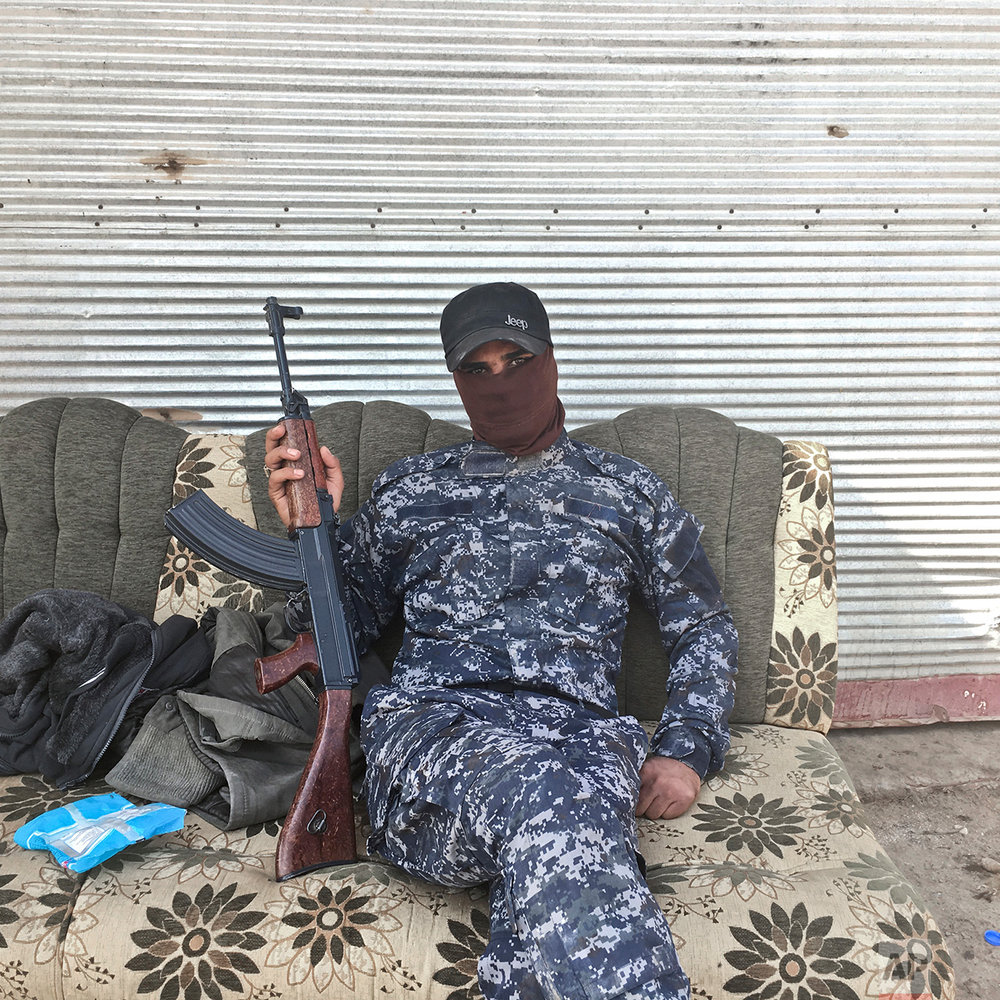 In this photo taken Thursday, Oct. 27, 2016,  Abdelyusef, no last name given, an Iraqi Federal Police officer, poses for a portrait at a checkpoint in the village of Al Hut, some 40 kilometers south of Mosul, Iraq. The push to kick the Islamic State out of Mosul has brought together an eclectic mix of Iraqis, young and old, police and soldiers, and a variety of irregular uniforms and equipment. (AP Photo/Marko Drobnjakovic)