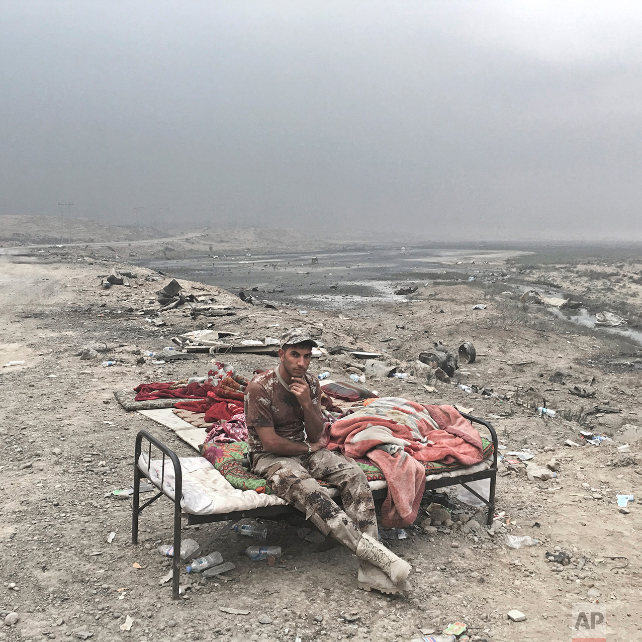 In this photo taken Wednesday, Oct. 26, 2016, Alaa Hashid, from Shura, Iraq, an Iraqi army soldier, poses for a portrait at a checkpoint in Qayara, some 50 kilometers south of Mosul, Iraq. The push to kick the Islamic State out of Mosul has brought together an eclectic mix of Iraqis, young and old, police and soldiers, and a variety of irregular uniforms and equipment. (AP Photo/Marko Drobnjakovic)