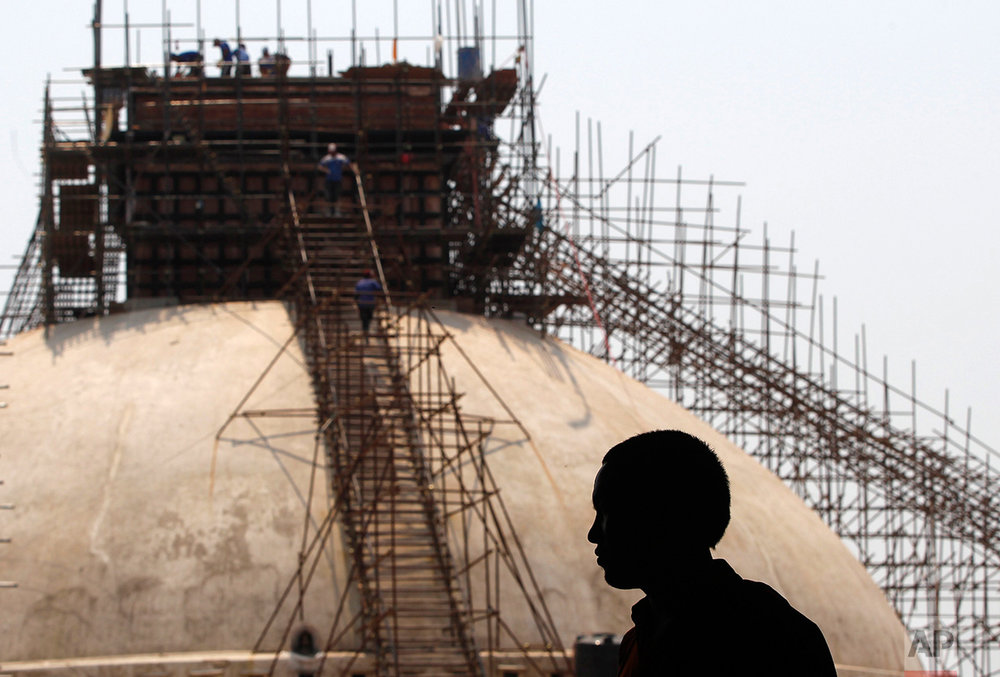 In this April 25, 2016 photo, a monk looks at the reconstruction work at the Boudhanath Stupa which was damaged in previous year's earthquake in Kathmandu, Nepal. A year and a half after a colossal earthquake destroyed hundreds of its treasured historic sites, Nepal on Tuesday celebrated the restoration of the iconic Buddhist monument topped in gold that towers above Kathmandu. (AP Photo/Niranjan Shrestha)