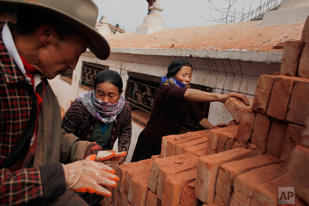 In this Jan. 12, 2016 photo, Nepalese people help voluntarily to reconstruct the Boudanath Stupa, which was damaged in the April 2015 earthquake in Kathmandu, Nepal. A year and a half after a colossal earthquake destroyed hundreds of its treasured historic sites, Nepal on Tuesday celebrated the restoration of the iconic Buddhist monument topped in gold that towers above Kathmandu. (AP Photo/Niranjan Shrestha)
