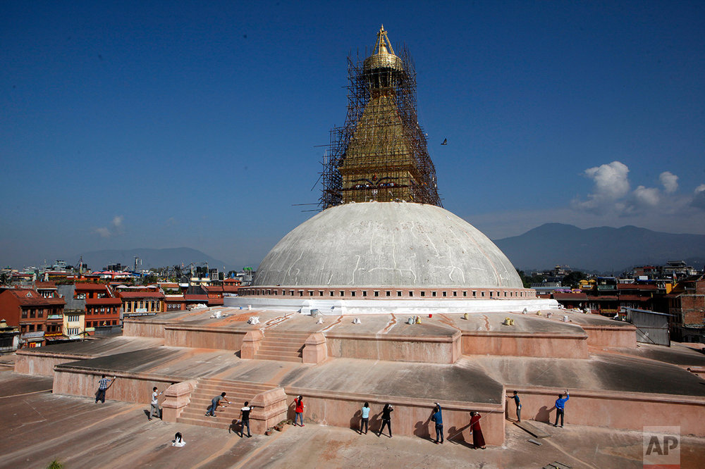 In this Oct. 20, 2016 photo, Nepalese volunteers work at the reconstruction site of Boudhanath Stupa in Kathmandu, Nepal. A year and a half after a colossal earthquake destroyed hundreds of its treasured historic sites, Nepal on Tuesday celebrated the restoration of the iconic Buddhist monument topped in gold that towers above Kathmandu. (AP Photo/Niranjan Shrestha)