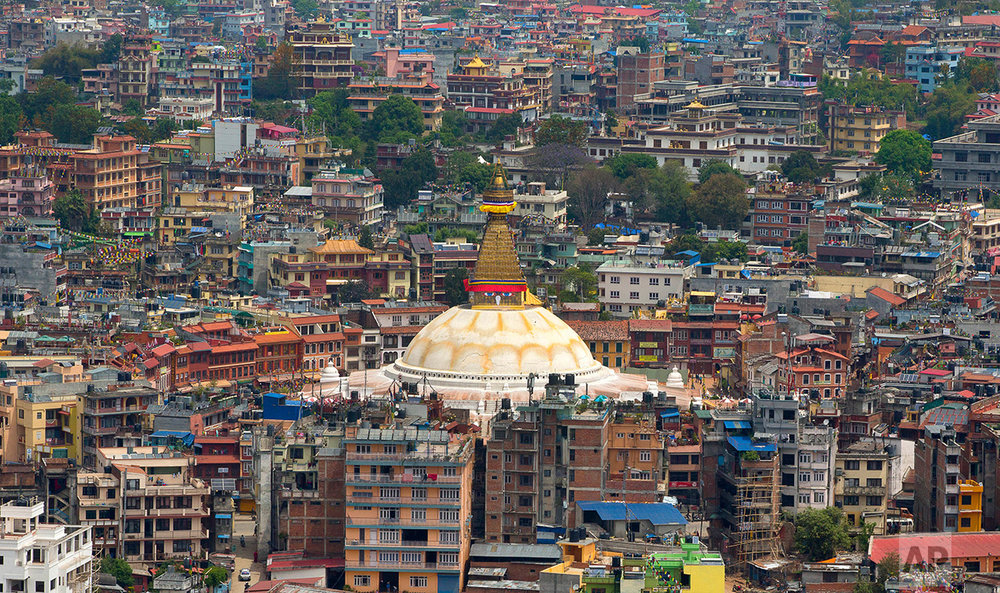 In this April 29, 2015 photo, the Boudhanath Stupa, center, stands amongst buildings four days after the April 25 massive earthquake in Kathmandu, Nepal.A year and a half after a colossal earthquake destroyed hundreds of its treasured historic sites, Nepal on Tuesday celebrated the restoration of the iconic Buddhist monument topped in gold that towers above Kathmandu. (AP Photo/Manish Swarup)