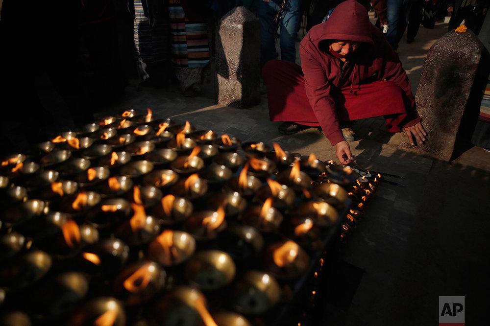A Buddhist monk lights butter lamp at the Boudhanath Stupa that was Tuesday opened to the public after restoration in Kathmandu, Nepal, Tuesday, Nov. 22, 2016. A year and a half after a colossal earthquake destroyed hundreds of its treasured historic sites, Nepal celebrated the restoration of the iconic Buddhist monument topped in gold that towers above Kathmandu. (AP Photo/Niranjan Shrestha)
