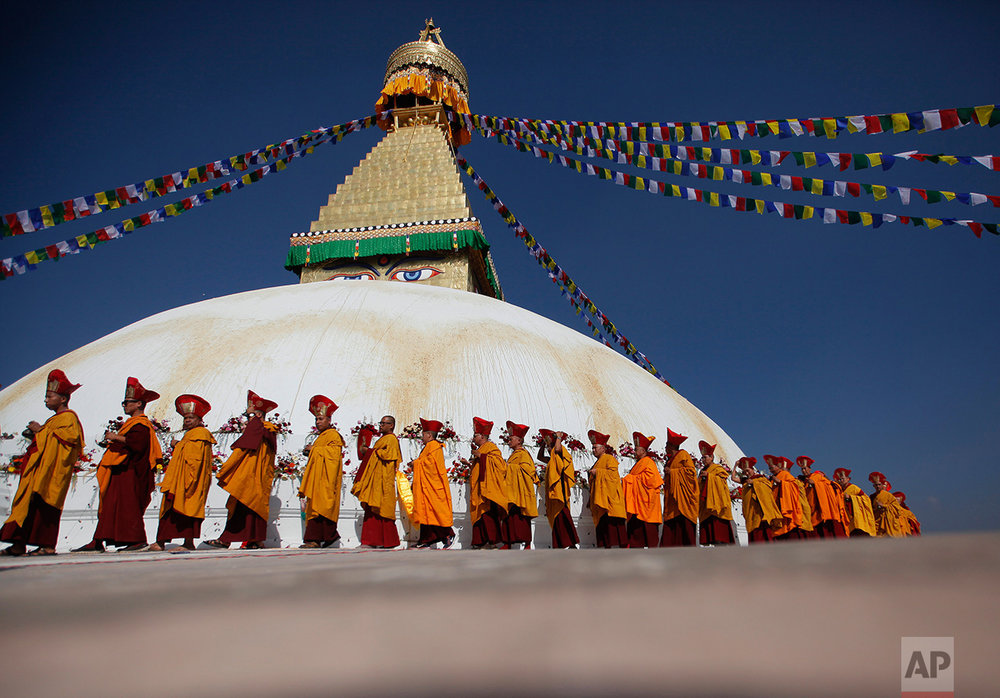 In this Nov. 20, 2016 photo, Buddhist monks circle around the Boudhanath Stupa during during the final day of its purification ceremony in Kathmandu, Nepal. A year and a half after a colossal earthquake destroyed hundreds of its treasured historic sites, Nepal on Tuesday celebrated the restoration of the iconic Buddhist monument topped in gold that towers above Kathmandu. (AP Photo/Niranjan Shrestha)