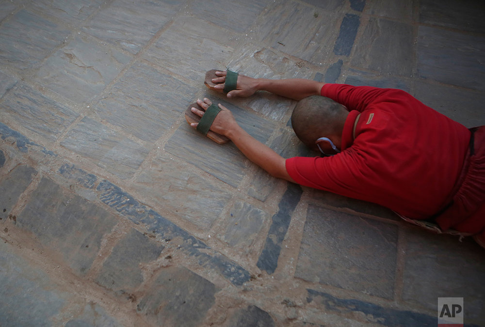 A Buddhist monk prostrates around the Boudhanath Stupa that was Tuesday opened to the public after restoration in Kathmandu, Nepal, Tuesday, Nov. 22, 2016. A year and a half after a colossal earthquake destroyed hundreds of its treasured historic sites, Nepal celebrated the restoration of the iconic Buddhist monument topped in gold that towers above Kathmandu. (AP Photo/Niranjan Shrestha)
