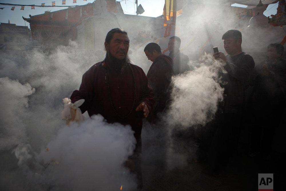 In this Nov. 20, 2016 photo, a Buddhist monk swings an incense burner as other Buddhists gather during the final day of the three-days purification ceremony of Boudhanath Stupa in Kathmandu, Nepal. A year and a half after a colossal earthquake destroyed hundreds of its treasured historic sites, Nepal on Tuesday celebrated the restoration of the iconic Buddhist monument topped in gold that towers above Kathmandu. (AP Photo/Niranjan Shrestha)