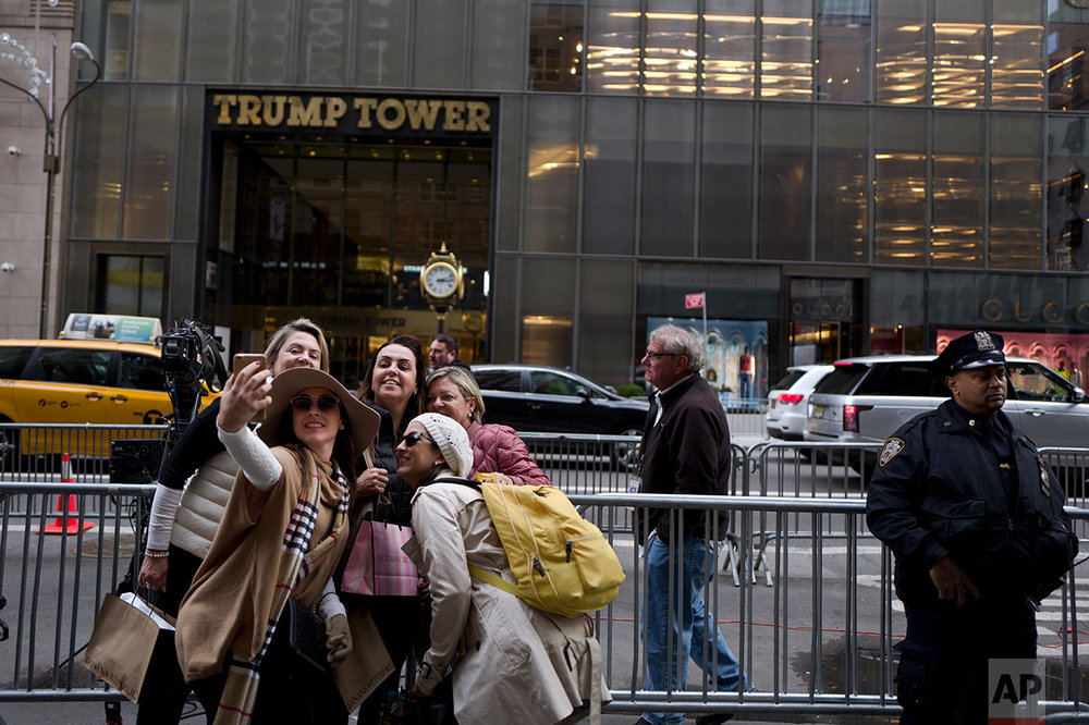 In this Wednesday, Nov. 16, 2016 photo, a group of women pose for a selfie outside Trump Tower in New York. (AP Photo/Muhammed Muheisen)