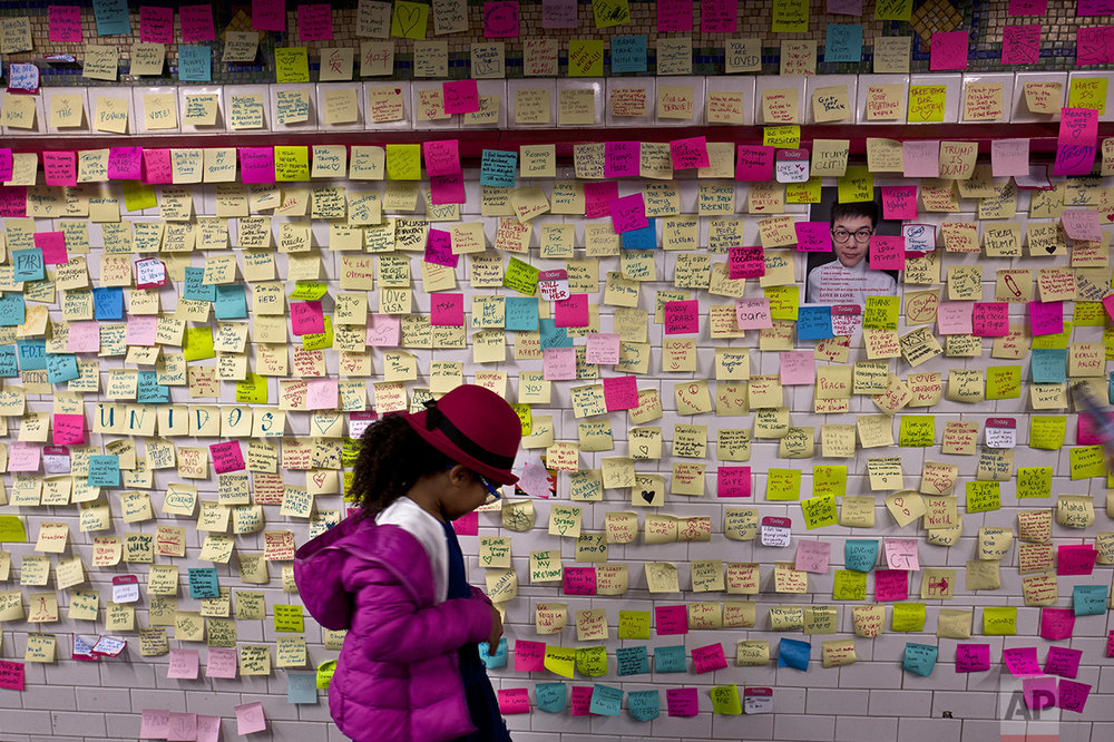 In this Sunday, Nov. 13, 2016 photo, a girl looks at anti- President-elect Donald Trump notes placed on a wall in the Union Square Subway Station in New York. (AP Photo/Muhammed Muheisen)