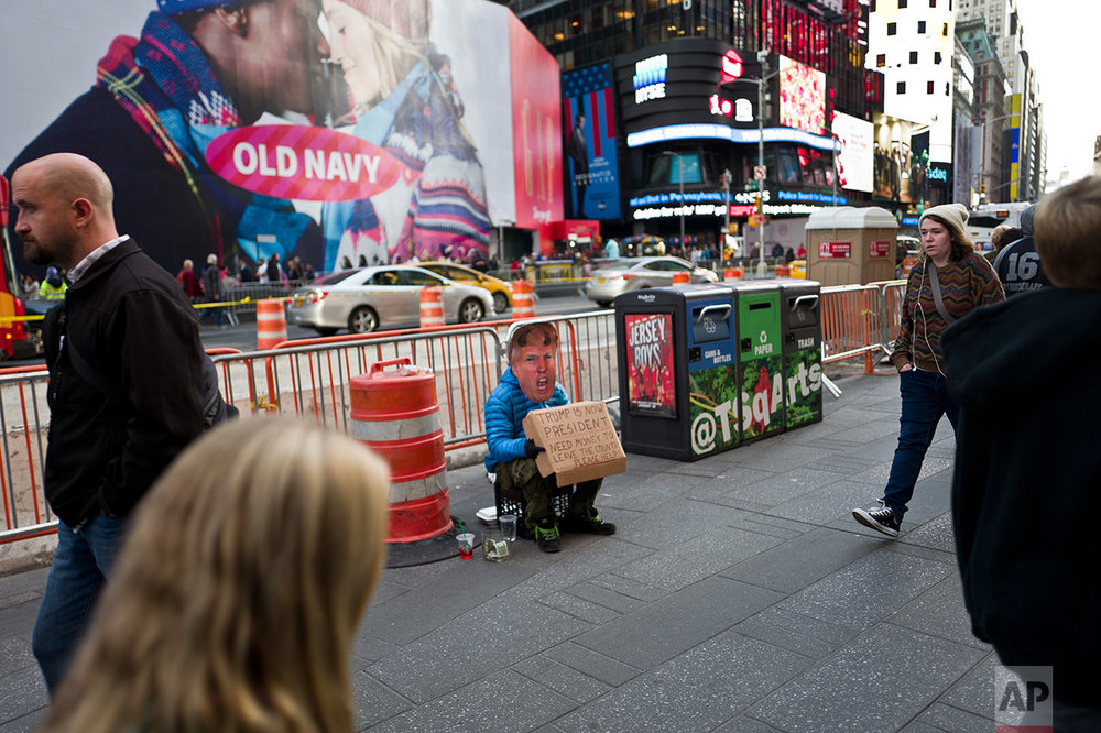 In this Thursday, Nov. 10, 2016 photo, a man wearing a mask showing President-elect Donald Trump sits on a sidewalk begging for money in New York. (AP Photo/Muhammed Muheisen)