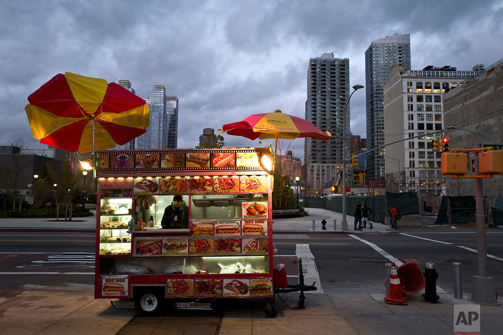 In this Sunday, Nov. 20, 2016 photo, a food vendor waits for customers on a roadside in New York. (AP Photo/Muhammed Muheisen)