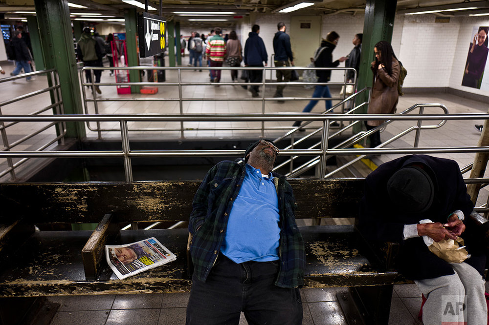 In this Monday, Nov. 14, 2016 photo, a newspaper featuring the image of President-elect Donald Trump on it's front page is left on a bench in a subway station in New York. (AP Photo/Muhammed Muheisen)