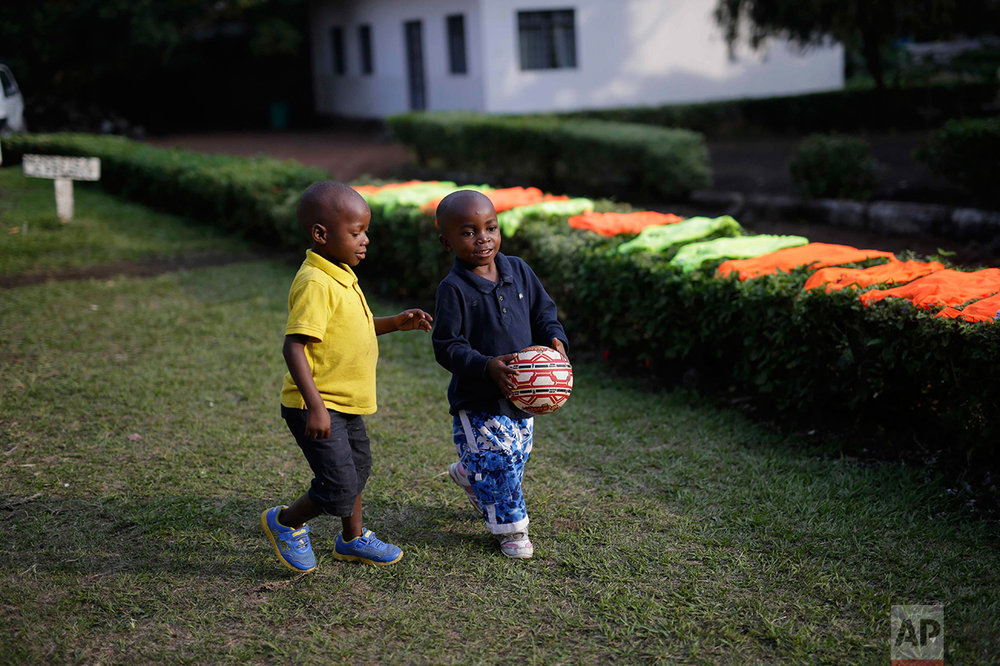 In this photo taken on Sunday, June 19, 2016, five-year-old Alpha Meleki, right, plays in the yard at the En Avant Les Enfants INUKA center in Goma, Democratic Republic of Congo. (AP Photo/Jerome Delay)