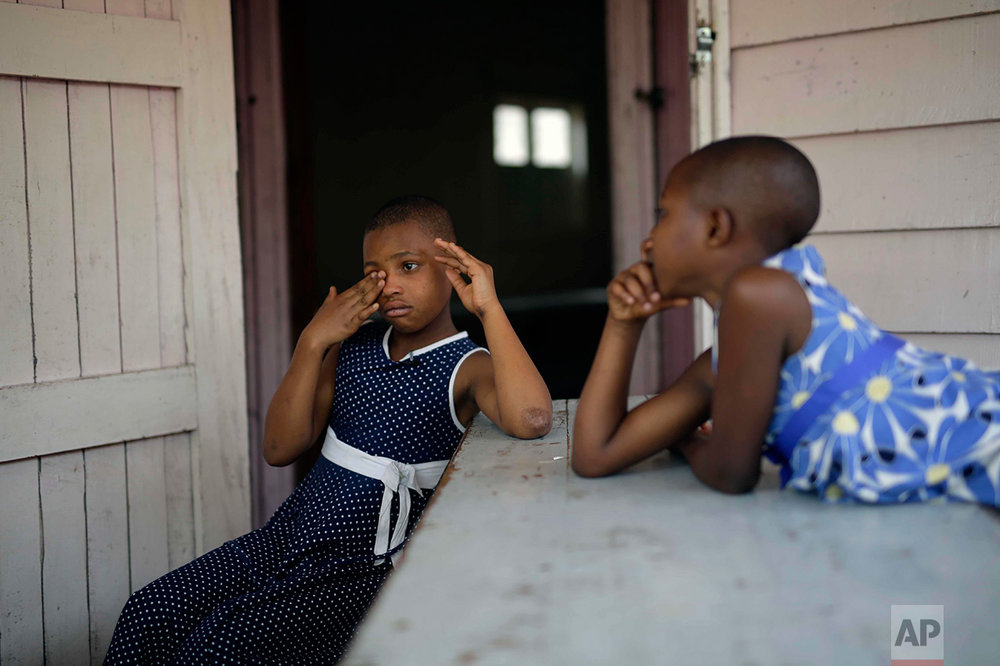 In this photo taken on Sunday, June 19, 2016, ten-year-old Safina Gatuku, left, and her sister Subiza, eight, sit in front of their room at the En Avant Les Enfants INUKA center in Goma, Democratic Republic of Congo. Abandoned by their father, they walked two days in the forest after their mother was killed by soldiers in 2009 before being pick-up by ICDC volunteers. (AP Photo/Jerome Delay)