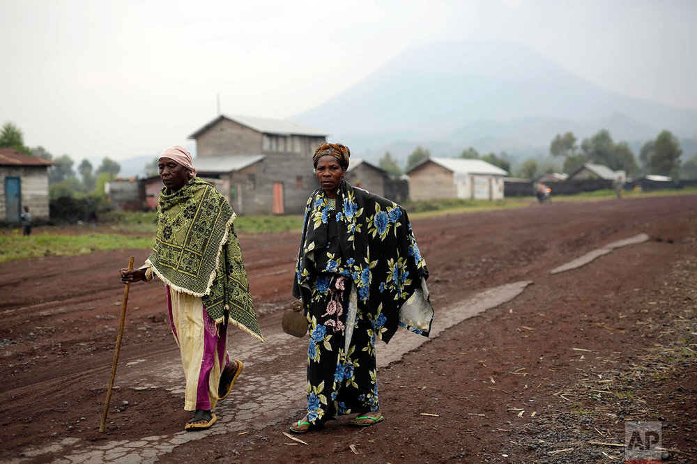 In this photo taken on Sunday, June 19, 2016, two elderly women walk in Goma, Democratic Republic of Congo. More than four million children have lost at least one parent in Congo over the past two decades. (AP Photo/Jerome Delay)