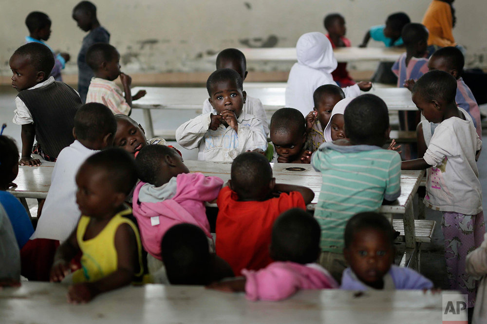 In this photo taken on Saturday, June 18, 2016, orphans eat their lunch at the Don Bosco center in Goma, Democratic Republic of Congo. (AP Photo/Jerome Delay)