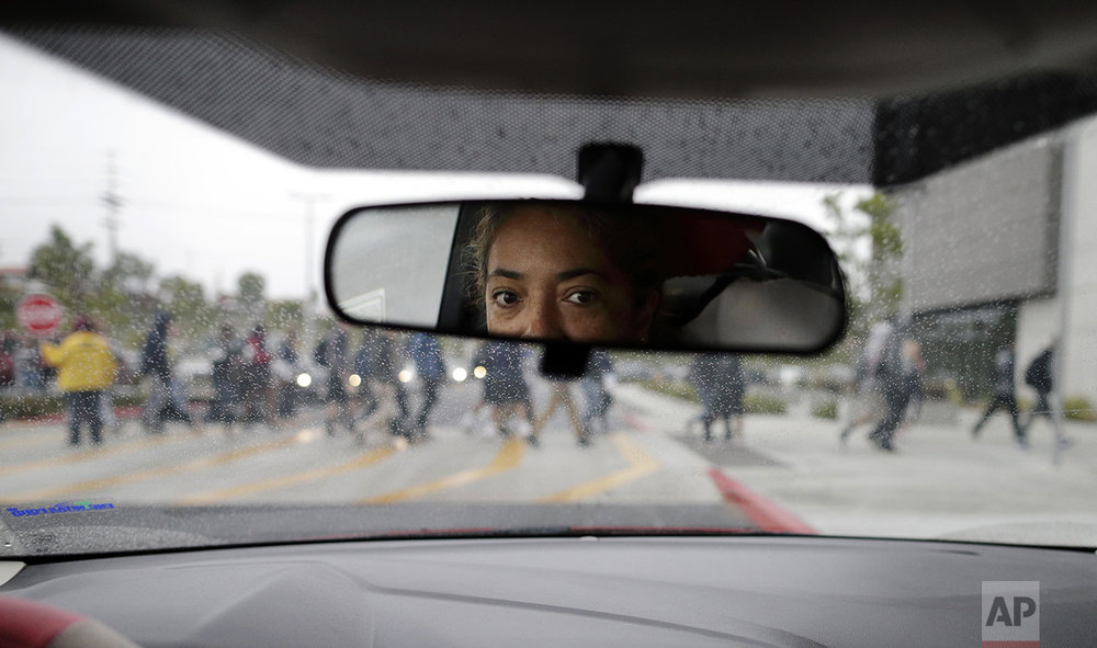 "Maribel Solache watches her son from her rearview mirror after dropping him off at his high school in San Marcos, Calif., on April 28, 2016. Moments before, Solache had been chatting and laughing with her son, but her light-heartedness changed after he got out and the distance grew between them. ""I cannot imagine my life without my kids, without my husband, and I am so afraid to be separated from them _ in front of them _ like for example if immigration stops me or the police stop me,"" she said. ""But I also fear bringing my kids back to Mexico, because the situation is terrible there."" A former Mexico City lawyer, Solache crossed the border illegally 12 years ago because of the country's drug violence. (AP Photo/Gregory Bull)"