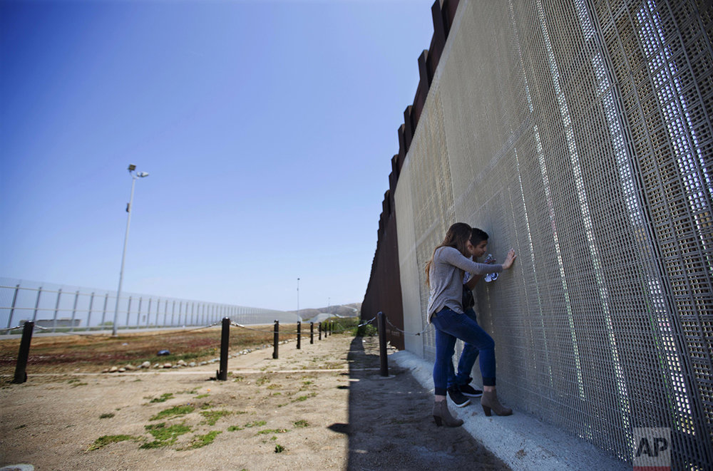 "On her 21st birthday, Eva Lara and her brother, Bryan, talk through a border fence in San Diego to their grandmother, Juana Lara, standing on the Mexican side, on Sunday, May 1, 2016. It was the first time Eva had seen her grandmother since she left Mexico at the age of 3 with her parents. Eva lives in the United States legally through legislation that temporarily prevents young immigrants from being deported. ""This was probably the best birthday gift I could get, you know, just seeing her. It was very emotional,"" she said. ""It was too much to take in, very overwhelming."" (AP Photo/Gregory Bull)"