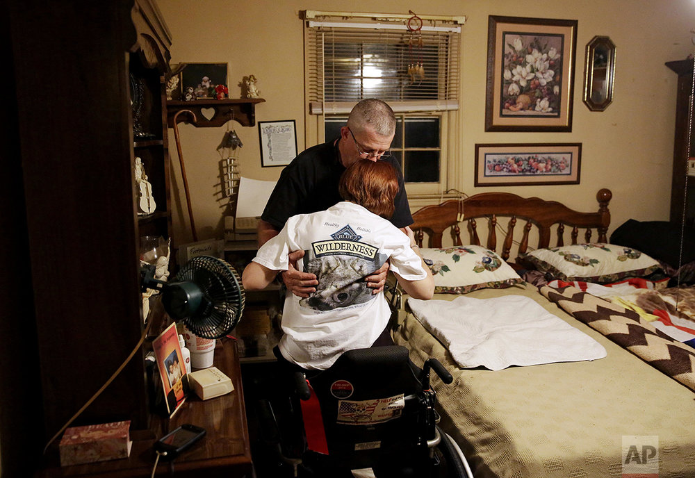 "Billy Inman kisses the forehead of his wife, Kathy, as he lifts her out of her wheelchair to help her into bed at their home Friday, May 27, 2016, in Woodstock, Ga. In 2000, a Mexican national in the country illegally crashed his vehicle into one driven by Billy who had stopped for a red light. The impact killed the Inman's 16-year-old son, Dustin, and the family dog and left Kathy with serious injuries. Since then, the Inmans have become involved in seeking stricter enforcement of laws to combat illegal immigration. ""I miss the hugs. I always got a hug from my son before going to bed,"" said Billy. ""Breaks my heart he's been gone 16 years and nothing else has been done. His killer is still walking around. It's not right."" (AP Photo/David Goldman)"