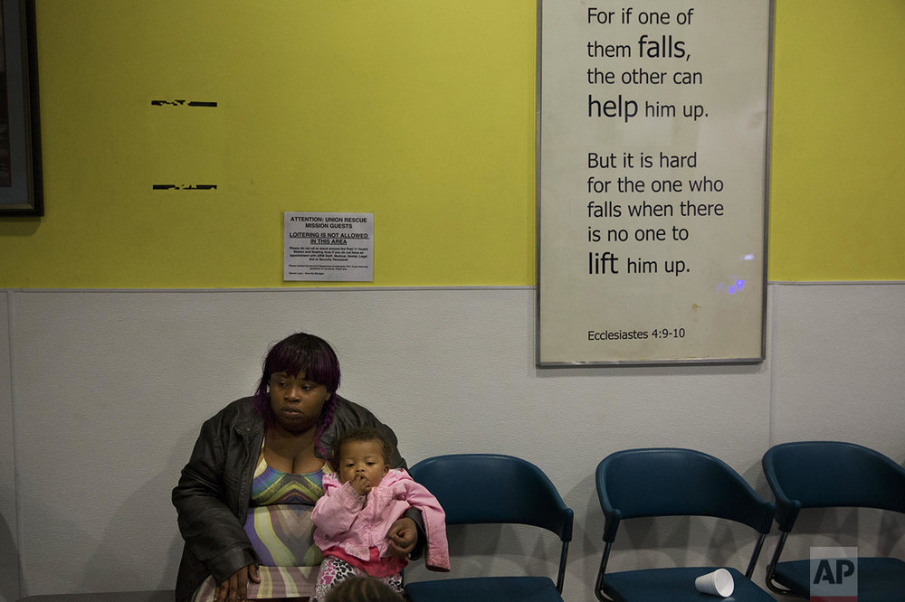 "Mariah Griffin-Hernandez, 25, sits with her 1-year-old daughter, Xy-lena, as she waits for her husband, James, in the lobby of the Union Rescue Mission in Los Angeles on Thursday, May 5, 2016. Originally from Houston, they moved to California this year with their two daughters to try to find a better future for their family. They want to make enough money to rent a small apartment, but at the moment, they're staying at a family shelter on Skid Row. ""Being homeless is very depressing. I feel like I couldn't take care of my family, but also being on Skid Row is very depressing, looking at all these people out here addicted to drugs,"" said James. (AP Photo/Jae C. Hong)"