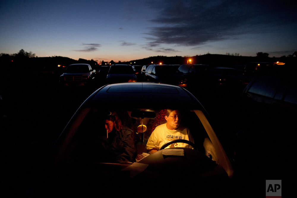 "Lesia Crigger, 47, left, of Woodlawn, Va., who is hoping to get fitted for dentures, lights a cigarette while waiting with her sister, Rhonda Gravley, 52, of Galax, Va., in a car overnight for the opening of the Remote Area Medical event at dawn Friday, April 29, 2016 in Smyth County, Va. Hundreds of others also waited overnight. Gravley, who is attending for the first time, is also hoping to go the dental clinic. Neither have dental insurance and cannot afford to pay for it on their own. ""I want all of my teeth pulled,"" says Gravley, ""they're all hurting me."" She ended up having several pulled by volunteer dentist Mark Copas. ""I've done foreign volunteer missions before,"" says Copas, ""but never domestic. These cases are just as bad as what I've seen in third world countries."" RAM provides free medical care to people in isolated and poverty stricken communities who do not have health insurance, in several states across the U.S. (AP Photo/Jacquelyn Martin)"
