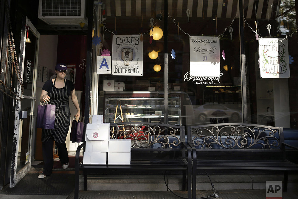 "Buttermilk Bakeshop owner Katie Rosenhouse carries a wholesale order to a customer at her bakery, Wednesday, May 11, 2016 in the Brooklyn borough of New York. Rosenhouse employs 14 hourly workers both full and part time for two bakeshops in the Park Slope neighborhood. While she understands that the minimum wage needs to be raised, she feels $15 is too high for a small business owner and the raise would affect the price of her product and also cut the number of people she can employ. ""Small bakeries can't afford to pay people that much... That's a lot of money when you're selling cupcakes. That's a lot of cupcakes,"" she says. ""It's great to pay people well when you're in business, but if you're out of business no one is making anything."" (AP Photo/Julie Jacobson)"