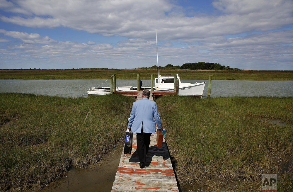 "In this May 15, 2016 photo, Rev. Rick Edmund walks to a boat that will take him to a church service in the community of Tylerton on Smith Island, Md. As the pastor of the island's three United Methodist churches, he preaches in each one every Sunday, making his circuit by golf cart and boat. Located less than four hours from Washington, and perched in the middle of the Chesapeake Bay, Smith Island is so isolated that many of its residents still bear a unique accent that descended from its first European settlers 400 years ago. Its population, which has dwindled to a few hundred and is largely dependent on commercial fishing, is threatened by a combination of sea level rise and erosion. A sticker on his guitar case bears a quote by Native American Chief Seattle: ""The Earth does not belong to us. We belong to the Earth."" Edmund says the impact of climate change is going to be felt for centuries. (AP Photo/Patrick Semansky)"