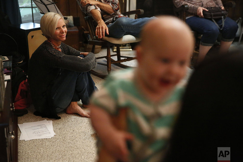 "Denise Wilkes, left, looks at baby Noah Burton sitting on a fellow worshiper's lap during a church service in Birmingham, Ala., on Sunday, May 22, 2016. Wilkes, 46, an anti-abortion, Christian musician and mother, had two abortion procedures when she was young, and now says she has had a change of heart and regrets her past decisions. ""I want people to see me as God sees me - a broken and lost vessel who made a lot of bad choices, including abortion, and was in need of a Savior. I have His forgiveness of sin through the death and resurrection of Jesus,"" she says. Wilkes now plays her guitar in front of Planned Parenthood in an effort to go into an area filled with death and release the sound of life through music and also to face her own past, she says. (AP Photo/Brynn Anderson)"