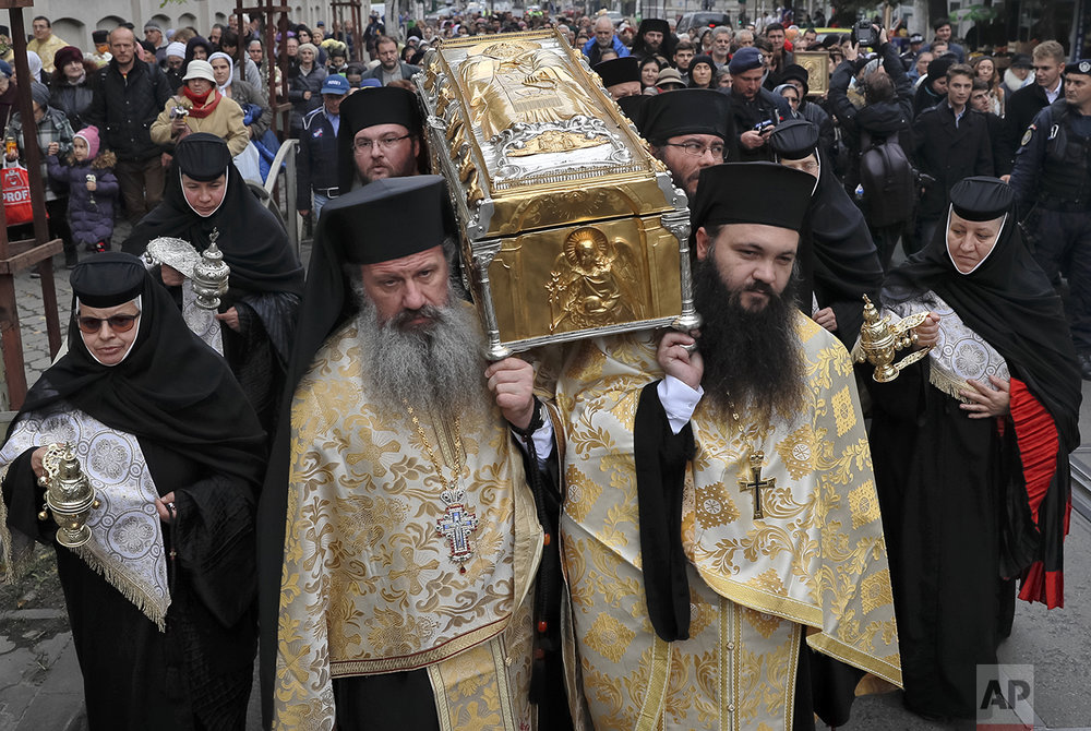 In this Saturday, Oct. 22, 2016 picture, priests carry the remains of Saint Dimitrie Bassarabov, during a pilgrimage, in Bucharest, Romania. The Romanian Orthodox and Catholic churches staged pilgrimages parading holy remains. The Catholics have a few drops of the blood of Saint John Paul II; the Orthodox claim to have the remains of three saints including those of St. Dimitrie, the patron saint of Bucharest. (AP Photo/Vadim Ghirda)
