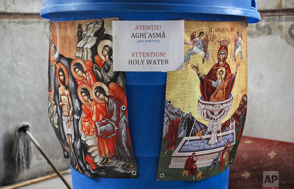 In this Saturday, Oct. 22, 2016 picture, a container holding holy water is placed at the entrance of the orthodox patriarchal cathedral in Bucharest, Romania. The feast of St. Dimitrie of Basarobov in Bucharest is an annual demonstration of the strength of Christianity in Romania, and the dominance of the Orthodox branch. (AP Photo/Vadim Ghirda)