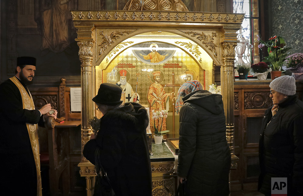 In this Saturday, Oct. 22, 2016 picture, women pass by a container holding remains of Saint Dimitrie Bassarabov, before they are taken out for a pilgrimage, at the orthodox patriarchal cathedral in Bucharest, Romania. (AP Photo/Vadim Ghirda)