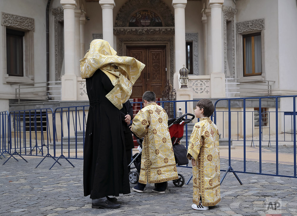 In this Saturday, Oct. 22, 2016 picture, children wearing orthodox priest outfits watch a priest getting into his outfit in Bucharest, Romania. The feast of St. Dimitrie of Basarobov in Bucharest is an annual demonstration of the strength of Christianity in Romania, and the dominance of the Orthodox branch. Catholics are 4.3 percent of Romania's population of 19 million, while about 85 percent are Orthodox believers. (AP Photo/Vadim Ghirda)