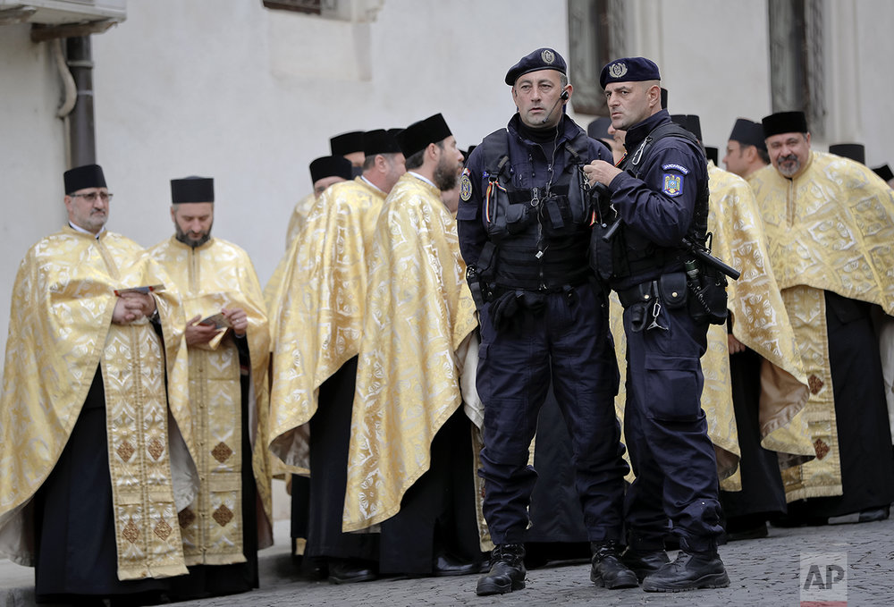 In this Saturday, Oct. 22, 2016 picture, riot police officers stand next to Orthodox priests before a pilgrimage, in Bucharest, Romania. The Romanian Orthodox and Catholic churches staged pilgrimages parading holy remains. (AP Photo/Vadim Ghirda)