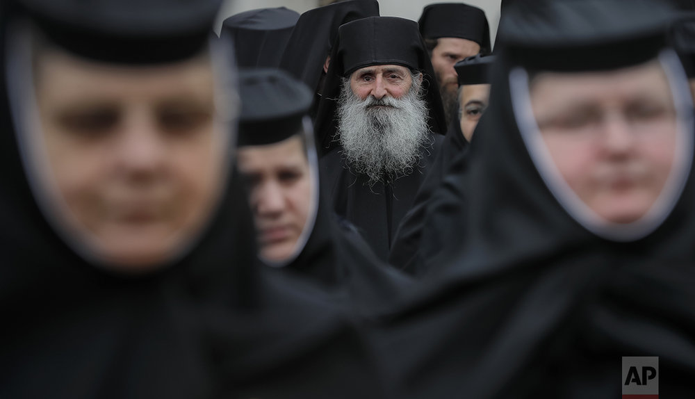 In this Saturday, Oct. 22, 2016 picture, Orthodox nuns and priests wait before a pilgrimage, in Bucharest, Romania. Both churches parade holy remains. The Catholics have a few drops of the blood of Saint John Paul II; the Orthodox claim to have the remains of three saints including those of St. Dimitrie, the patron saint of Bucharest. (AP Photo/Vadim Ghirda)