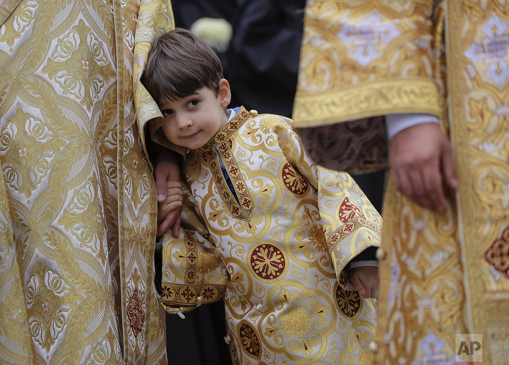 In this Saturday, Oct. 22, 2016 picture, a child wearing a priest outfit holds the hand of an Orthodox priest before a pilgrimage, in Bucharest, Romania. Both churches parade holy remains. The Catholics have a few drops of the blood of Saint John Paul II; the Orthodox claim to have the remains of three saints including those of St. Dimitrie, the patron saint of Bucharest. (AP Photo/Vadim Ghirda)